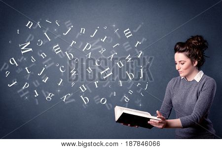 Casual young woman holding book with white letters flying out of it