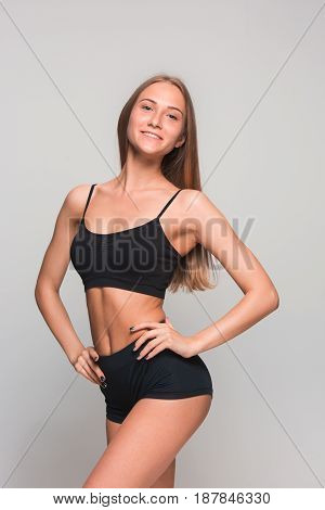 Muscular young woman athlete posing on gray studio background