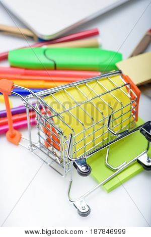 Different Colorful School Supplies Spilled Out Of Little Shopping Cart Isolated On White