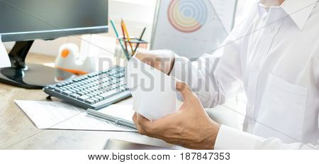 Businessman opening envelope at working desk in the office - panoramic banner selective focus