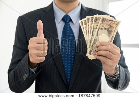 Businessman showing money Japanese yen banknotes and giving thumbs up