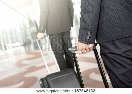 Businessmen pulling baggage while walking at the airport - business travel concept