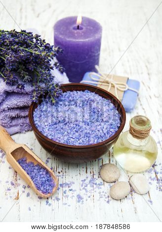 Lavender sea salt and candle on a wooden background