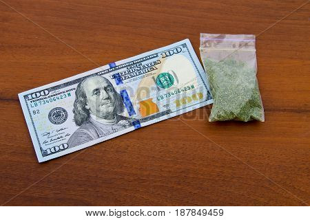 Marijuana In Packet And 100 Dollar Bill On Wooden Table