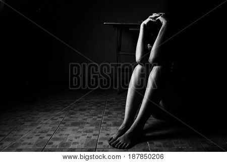 a woman sitting on ground with arm around lower head sexual violence sexual abuse human trafficking concept with shadow edge in white tone