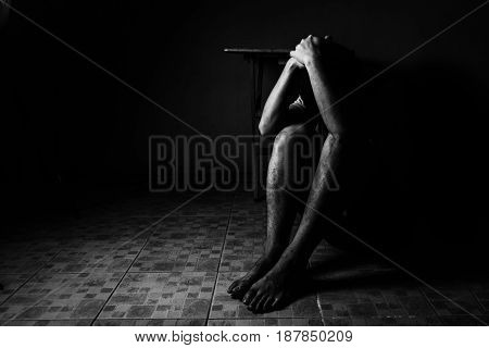 a man sitting on ground with arm around lower head sexual violence sexual abuse human trafficking concept with shadow edge in white tone