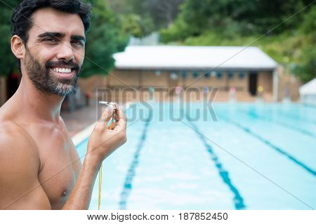 Portrait of smiling lifeguard standing with whistle near poolside