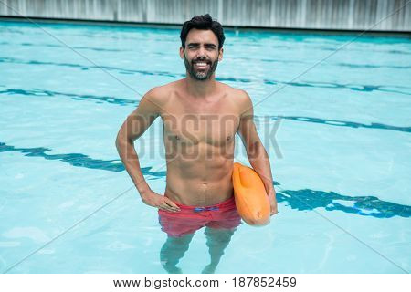 Portrait of man standing in swimming pool with rescue buoy