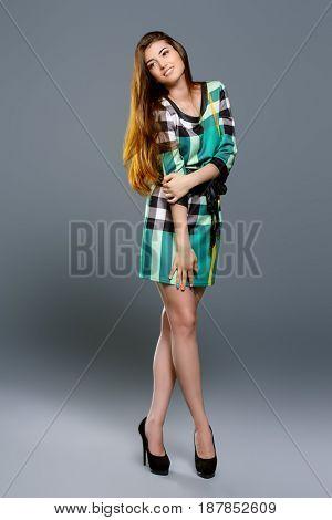 Fashion shot of a beautiful young woman with charming smile wearing summer dress. Studio shot.