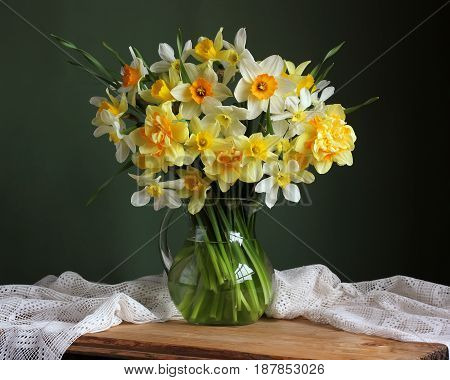 Varietal yellow daffodils in a jug on table with white tablecloth against a green background.