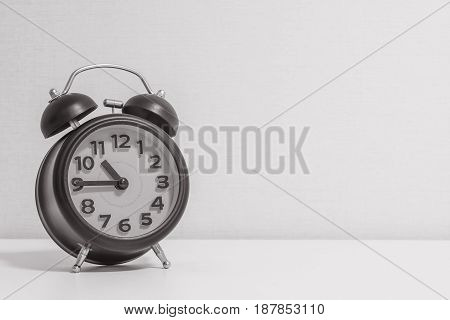 Closeup alarm clock for decorate show a quarter to eleven o'clock or 10:45 a.m. on white wood desk and cream wallpaper textured background in black and white tone with copy space
