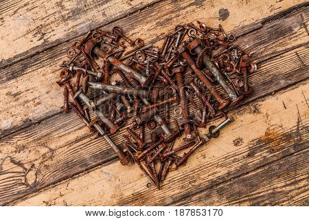 Heart of bolts and nuts on a wooden background.