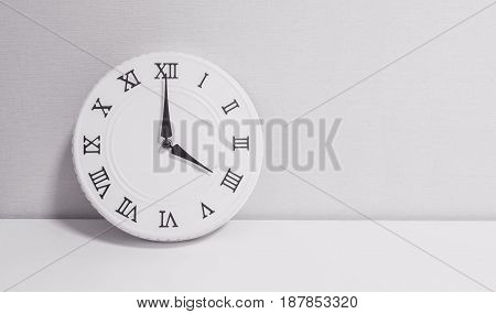 Closeup white clock for decorate in 4 o'clock on white wood desk and wallpaper textured background in black and white tone with copy space