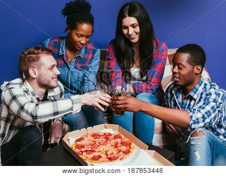 Young friends international company eat pizza with soda, cheers. Four happy people together, fun leisure, home party, unhealthy food concept.