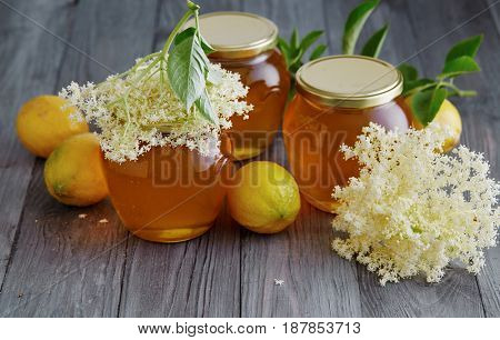 Elderflower and lemon jelly in jars on wooden table.