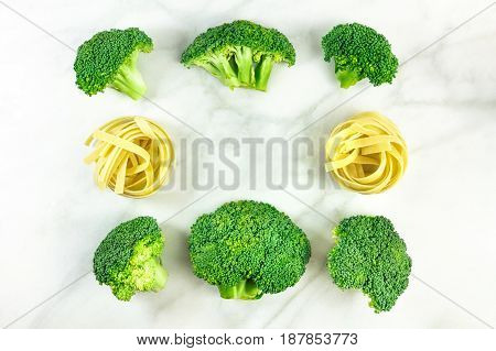 Vibrant green broccoli sprouts and pasta nests, shot from above on a white marble texture, forming a frame with a place for text