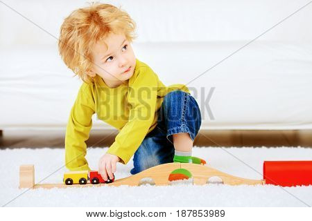 Cute 3 year old boy is playing with his toys at home. Happy childhood.