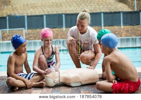 Female lifeguard assisting children during rescue training at poolside