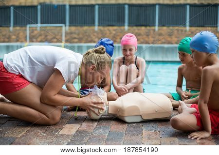 Side view of female lifeguard demonstrating children during rescue training