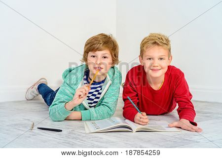 Two funny children doing home school task together. Educational concept.