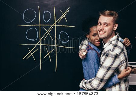Happy young interracial couple hug. Fun play tic tac toe game, man and woman happy together. Joy, smile and equality of the sexes, victory, support concept.