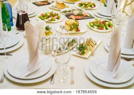 Close up image of served restaurant table with variety of salads, wineglasses and white textile napkins