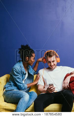 Young interracial couple in quarrel at home, white man ignore black woman. Wear headphones and look at phone, do not listen, relationship problem, inattentive concept.