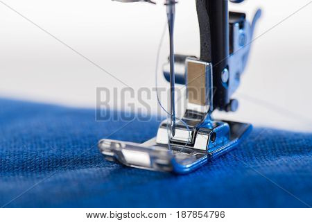 Close-up View Of Working Sewing Machine Sewing Blue Fabric