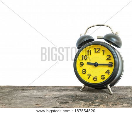 Closeup black and yellow alarm clock for decorate show a quarter past nine o'clock or 9:15 a.m. on old brown wood desk isolated on white background with copy space