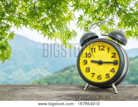 Closeup black and yellow alarm clock for decorate show a quarter past eight o'clock or 9:15 a.m. on blurred leaves and mountain view background
