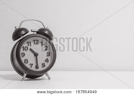 Closeup alarm clock for decorate show half past ten o'clock or 10:30 a.m.on white wood desk and cream wallpaper textured background in black and white tone with copy space