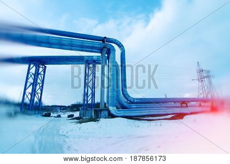 Industrial Zone, Steel Pipelines And Valves Against Blue Sky. Toned Image. Motion Blur Effect.