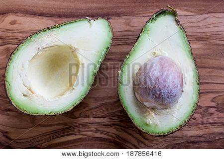 Two Halves Of A Ripe Avocado On A Wooden Background