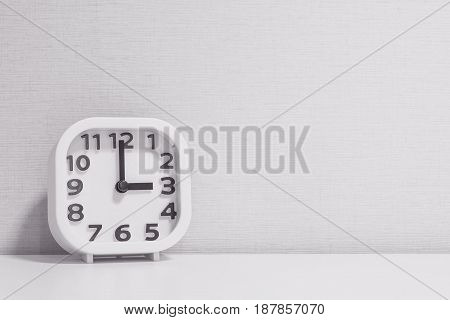 Closeup white clock for decorate in 3 o'clock on white wood desk and cream wallpaper textured background in black and white tone with copy space