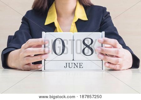 Closeup white wooden calendar with black 8 june word in blurred working woman hand on wood desk in office room in selective focus at the calendar