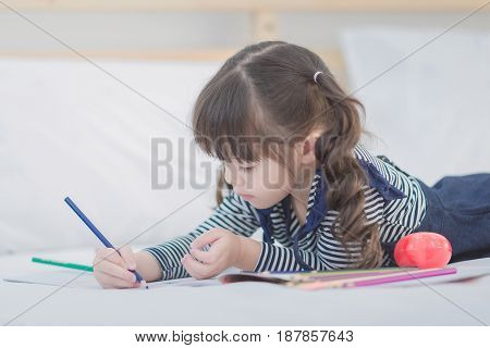 Cute Asian Little Girl Doing Homework,writing With Colourful Pencils On Bed At Home. Elegant Design