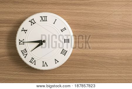 Closeup white clock for decorate show a quarter to eight o'clock or 7:45 a.m. on wood desk textured background with copy space
