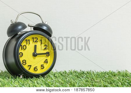 Closeup black and yellow alarm clock for decorate show a quarter past twelve o'clock or 12:15 p.m. on green artificial grass floor and cream wallpaper textured background with copy space