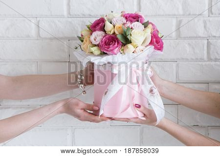Delivery of a floristry workshop. The customer receives his order-a bouquet of pink and pale yellow roses. Hand courier pass flowers to the buyer. Small business concept