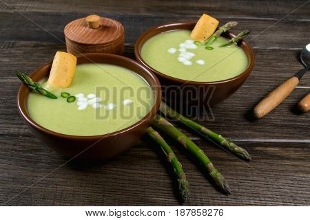 Green spring pureed  cream asparagus soup in ceramic bowl on dark wooden table