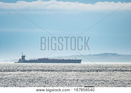 Dartmouth Massachusetts USA -- March 30 2013: Tug pushing barge through Buzzards Bay with Cuttyhunk Island in background