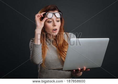 Shocking article. Expressive classy bright woman holding up her glasses while using her computer and looking amazed