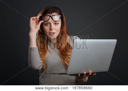 Savvy lady. Cute smart young woman using he laptop and holding up her glasses while standing isolated on grey background