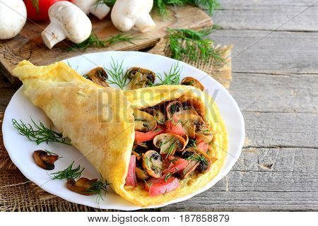 Mushrooms omelette with tomatoes. Homemade omelette with fried mushrooms, fresh tomatoes slices and finely chopped dill on a plate and on a wooden table. Fast and easy stuffed omelette. Rustic style
