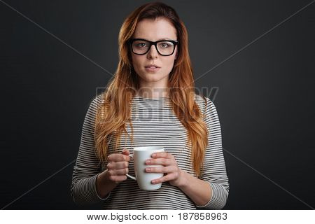 Warm drink. Cute enchanting young lady standing isolated on grey background while holding a cup in her hands and wearing glasses