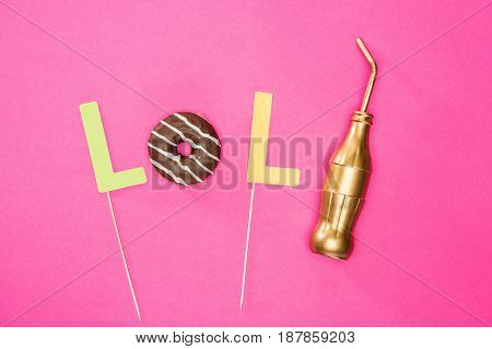 Food Composition Concept With Donut In Chocolate Glaze And Golden Bottle Isolated On Pink
