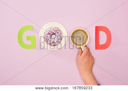 Top View Of Good Word Made From And Cup Of Coffee In Human Hand And Donuts Isolated On Pink. Donuts