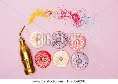 Top View Of Variety Frosted Donuts And Golden Bottle On Pink Surface. Donuts Chocolate Background