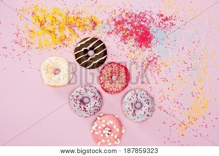 Top View Of Donuts With Different Sweet Glaze And Sprinkles On Pink.  Donuts Chocolate Background