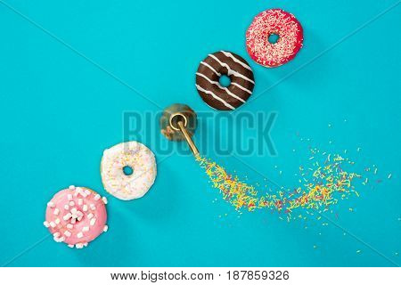 Overhead View Of Four Donuts With Colorful Glaze In Row. Donuts Isolated On Blue Background